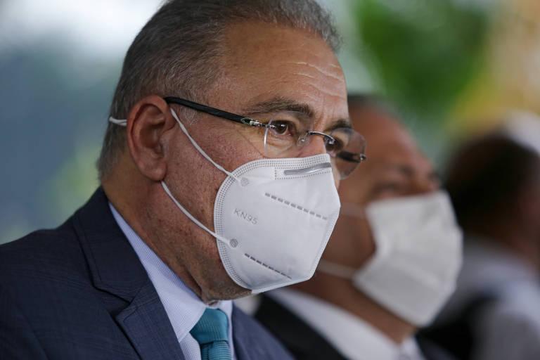 Marcelo Queiroga aparece do ombro para cima, de perfil, olhando para o lado direito. Ele está de máscara