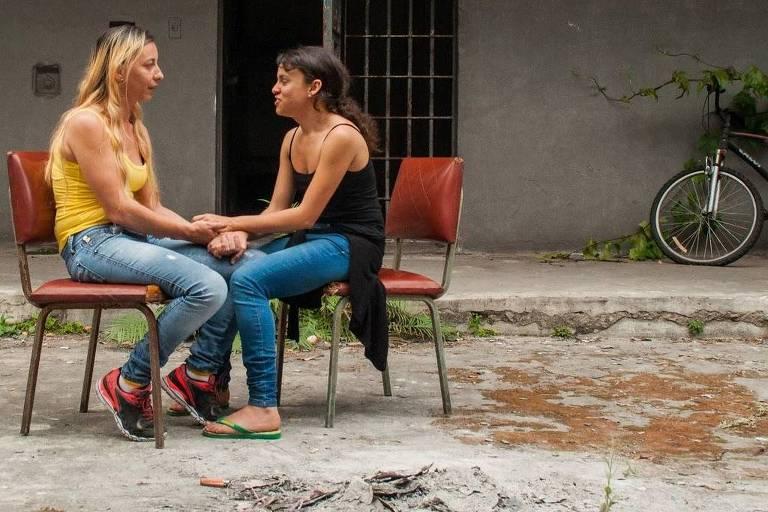 duas mulheres conversam em espaço externo, sentadas em cadeiras escolares