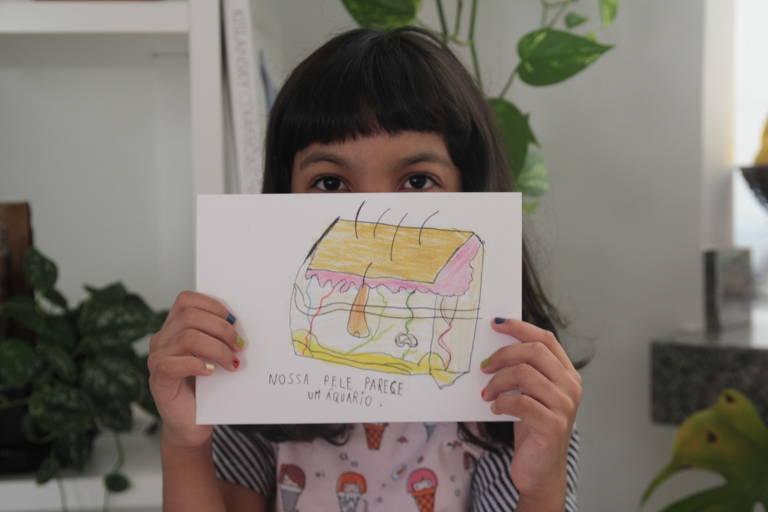 Menina de franja segura um de seus desenhos, com um recorte mostrando um pedaço de pele