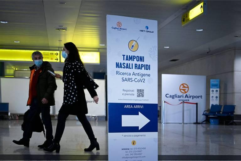 duas pessoas passam em saguão de aeroporto, atrás de placa que anuncia teste para covid