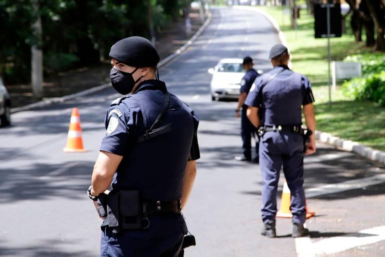 Imagem mostra guardas civis em rua para controlar a circulação de veículos; apenas um automóvel se aproxima deles