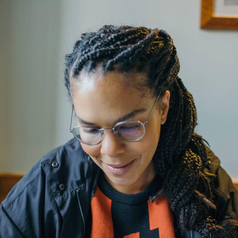 mulher negra de cabelos longos e usando óculos olhando para baixo