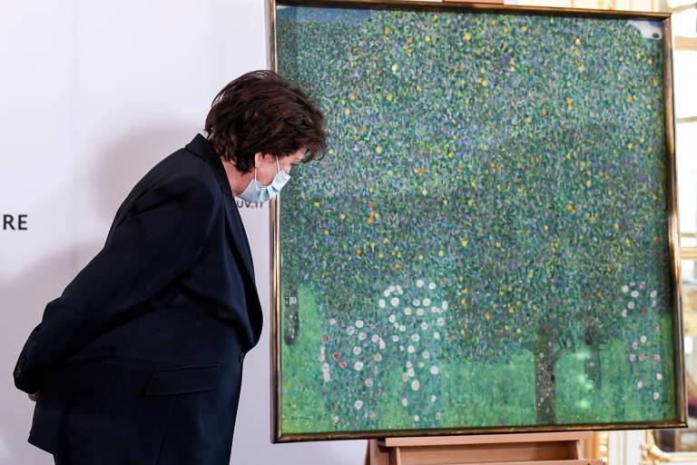 Mulher branca usa terno preto e máscara de proteção facial enquanto olha quadro que ilustra jardim com rosas