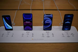FILE PHOTO: Apple's 5G iPhone 12 and iPhone 11 are seen at an Apple Store in Shanghai, China
