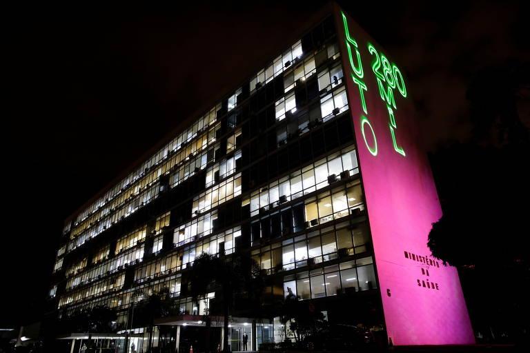 Prédio visto à noite com projeção verde e roxa em uma de suas paredes