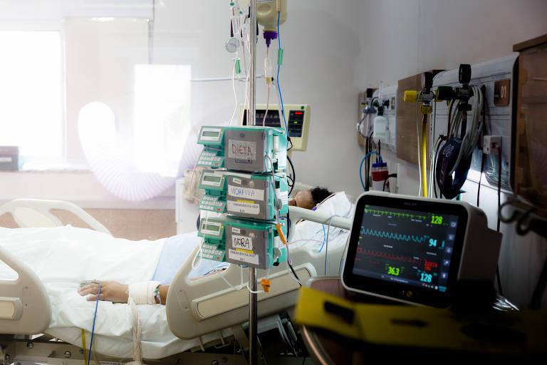 Aparelhos hospitalares em ambiente de UTI com cama com paciente ao fundo. Não é possível ver o rosto do paciente