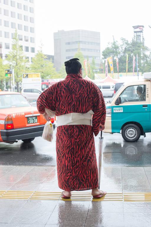 homem com kimono vermelho de costas diante de uma rua