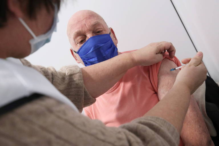 Enfermeira de casaco bege aplica injeção no braço esquerdo de homem de camiseta cor de salmão