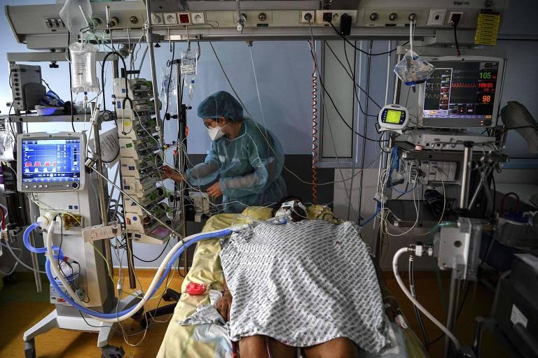 paciente deitado numa maca, cercado de vários equipamentos, com muitos tubos entrando e saindo de seu corpo, e enfermeira de azul ao fundo