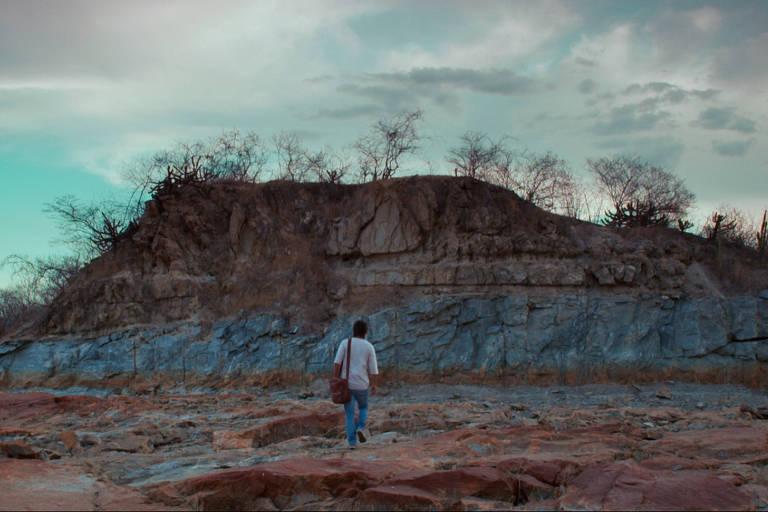 Homem em frente a uma grande montanha, repleta por uma vegetação seca