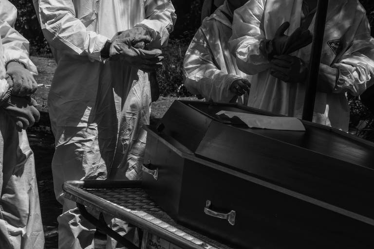 Sepultadores com as mãos juntas, na altura da cintura, em frente a um caixão