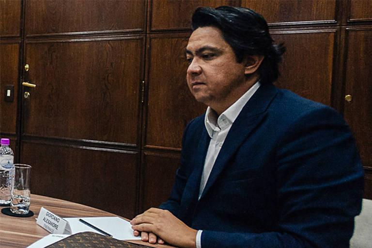 Homem de cabelos escuros vestindo paletó sentado com as mãos sobre uma mesa
