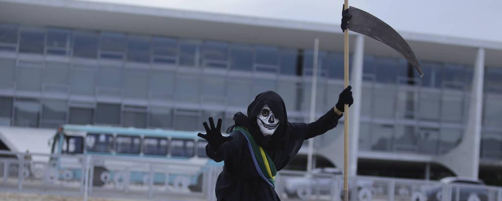 Manifestante em protesto em frente ao Planalto no qual chama o presidente Bolsonaro de genocida