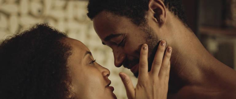 mulher e homem negros prestes a se beijar