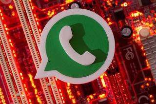 FILE PHOTO: A 3D printed Whatsapp logo is placed on a computer motherboard