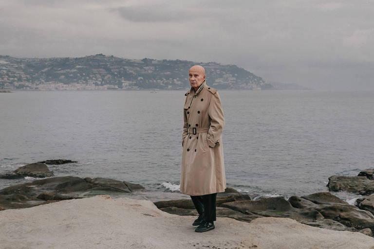 homem idoso usando casaco para chuva em cima de uma pedra com mar ao fundo