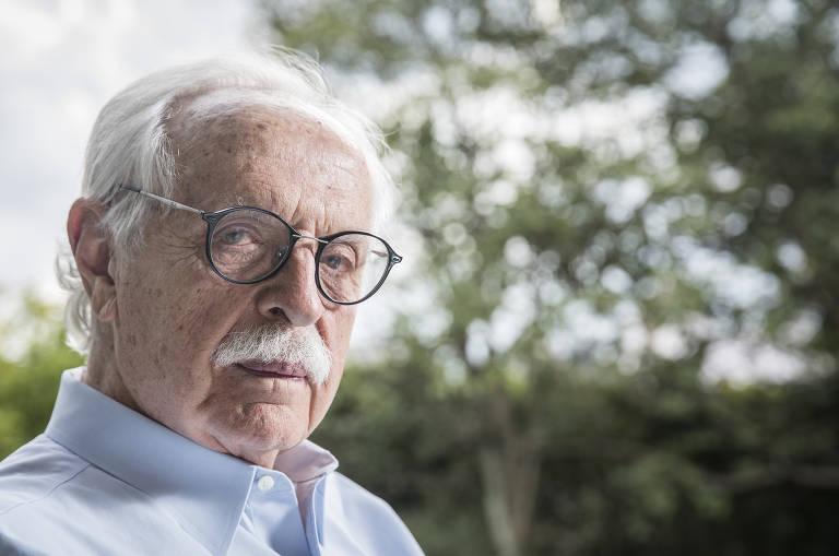 Homem de óculos, bigode e cabelos brancos olha para a câmera