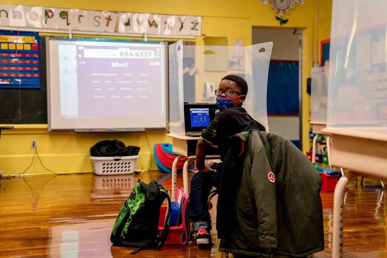 Aluno criança, de óculos, está sentado com a lousa à frente. Ele se vira para olhar para a câmera. A sala é de madeira e colorida. A mochila dele está no chão