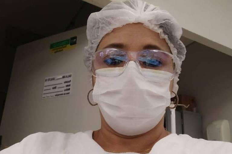 Mulher de máscara, touca e avental hospitalar faz selfie