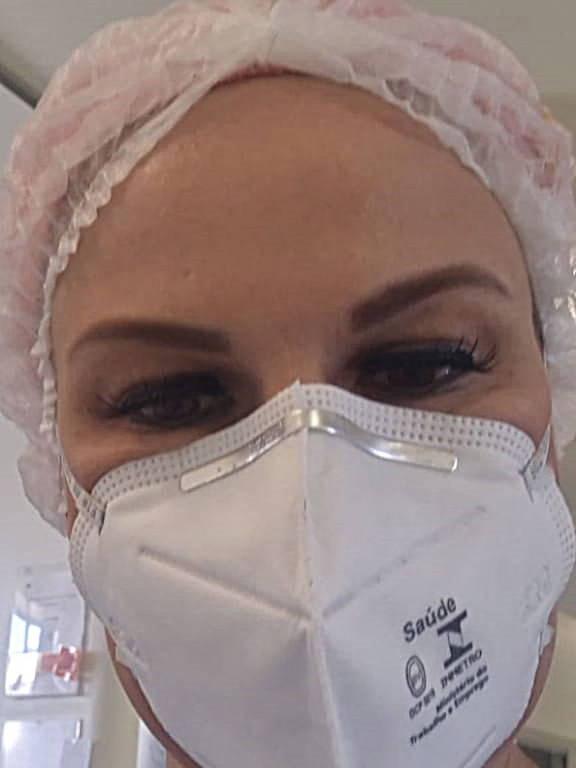 Mulher de máscara e touca faz selfie