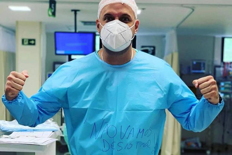 """Médico de máscara, touca e com avental escrito """"Não Vamos desistir"""" em UTI"""