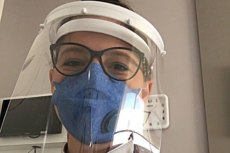 Mulher de máscara, óculos e capa acrílica no rosto faz selfie