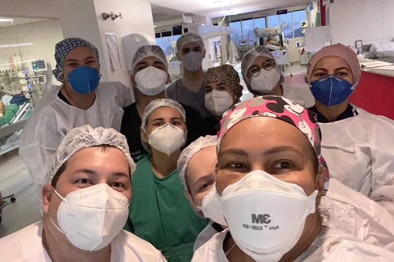 médicos com máscara e touca em UTI