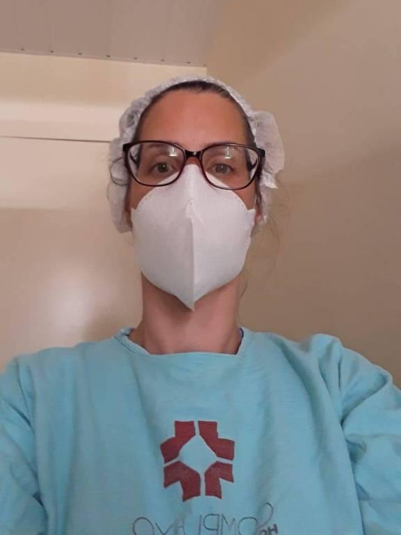 Médica paramentada com uniforme, touca e máscara de proteção