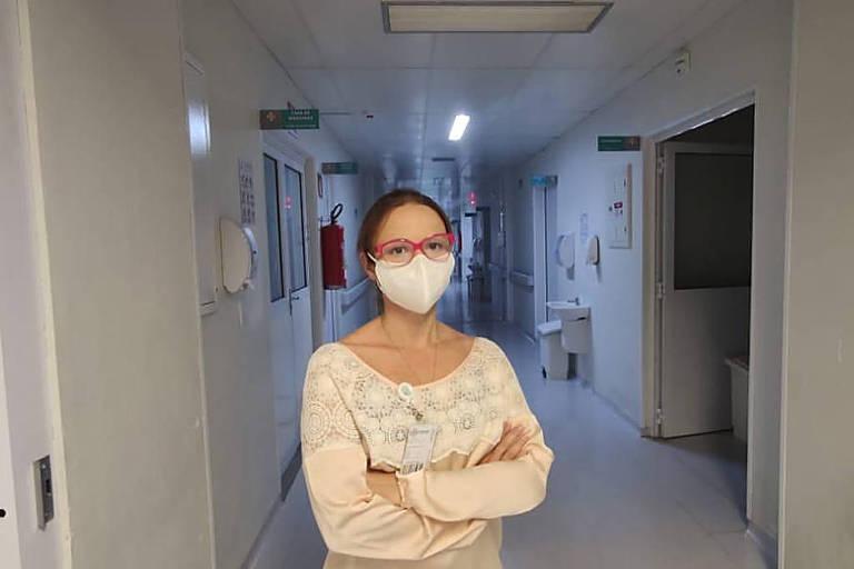 mulher de máscara em corredor de hospital