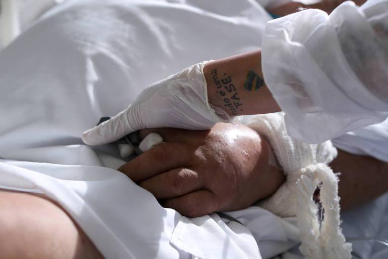 Enfermeira segura a mão de um paciente com Covid-19 na UTI do Hospital São Paulo