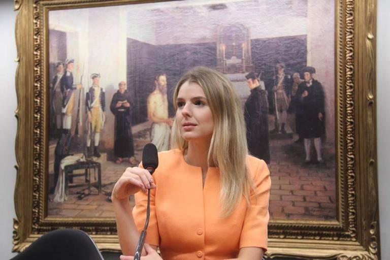 deputada de laranja segura um microfone na frente de um quadro