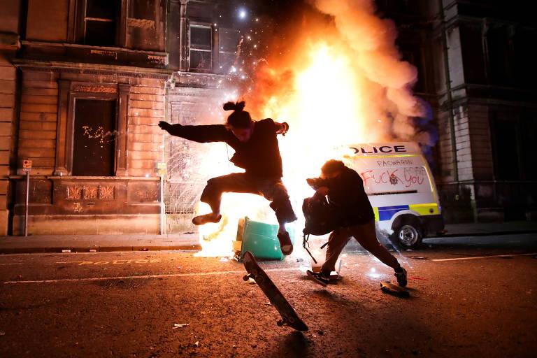 Homem salta de skate enquanto outro caminha, à noite, tendo ao fundo um carro de polícia que pega fogo