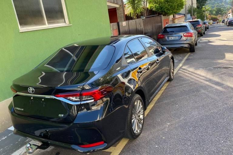 dois carros estacionados na rua