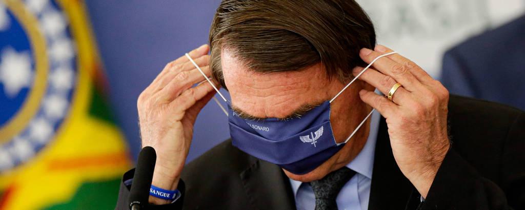 O presidente Jair Bolsonaro tenta colocar máscara da Aeronáutica em evento no Palácio do Planalto