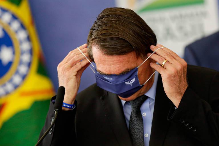 Bolsonaro tenta colocar uma máscara com brasão da FAB em evento no Palácio do Planalto