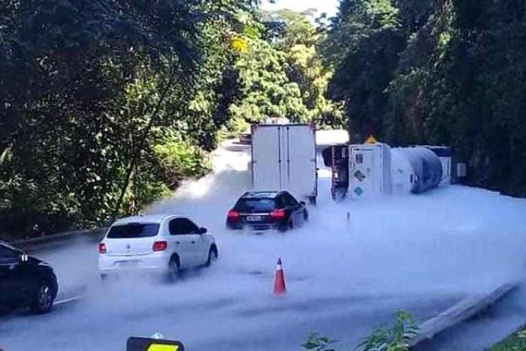 espuma na estrada com carros e um caminhão tombado.