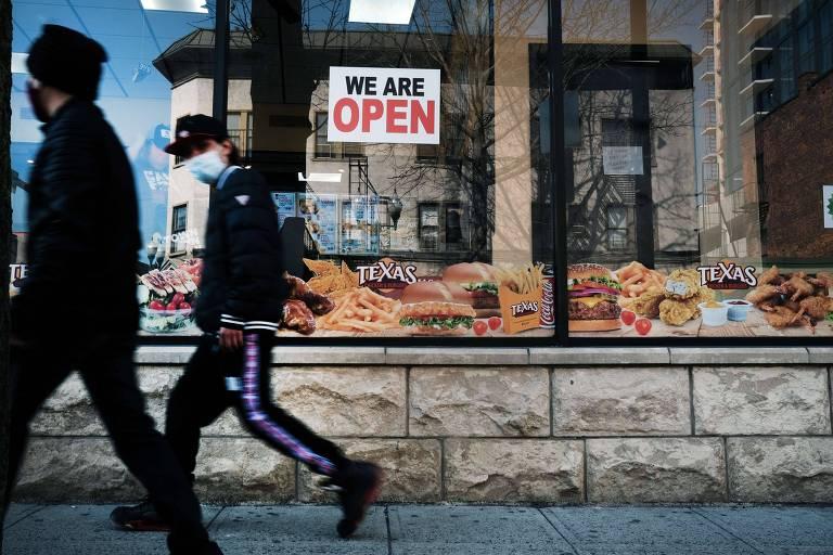 Pessoas caminham nas ruas da cidade de Rochelle, em Nova York; ao fundo, uma placa colada à vitrine de um restaurante diz 'estamos abertos'