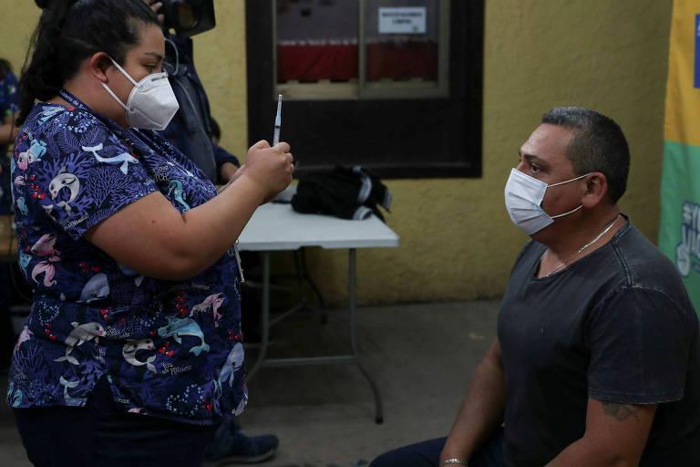 Profissional de saúde se prepara para administrar uma dose da vacina contra a Covid-19 a um morador de rua em Santiago