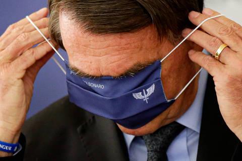 BRASÍLIA, DF, 22-03-2021 - O presidente Jair Bolsonaro tenta colocar máscara com brasão da FAB, durante anúncio de investimentos para o programa Águas Brasileiras, no Palácio do Planalto, em Brasília (DF). (Foto: Raul Spinassé/Folhapress)