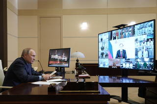 Russian President Vladimir Putin speaks during a video conference call outside Moscow