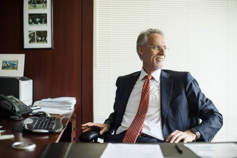 Homem branco, grisalho, de terno e gravata, sentado em mesa de escritório