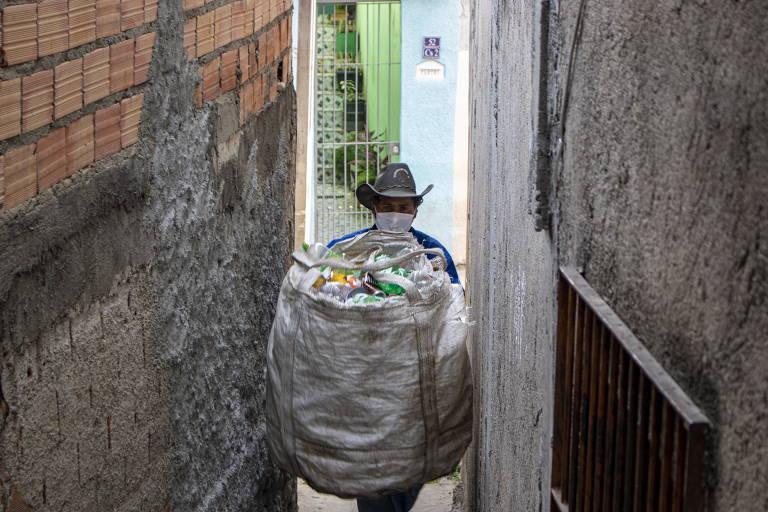 Homem com sacola cheia de material reciclável circula em via estreita. Ele está de chapéu e de costas