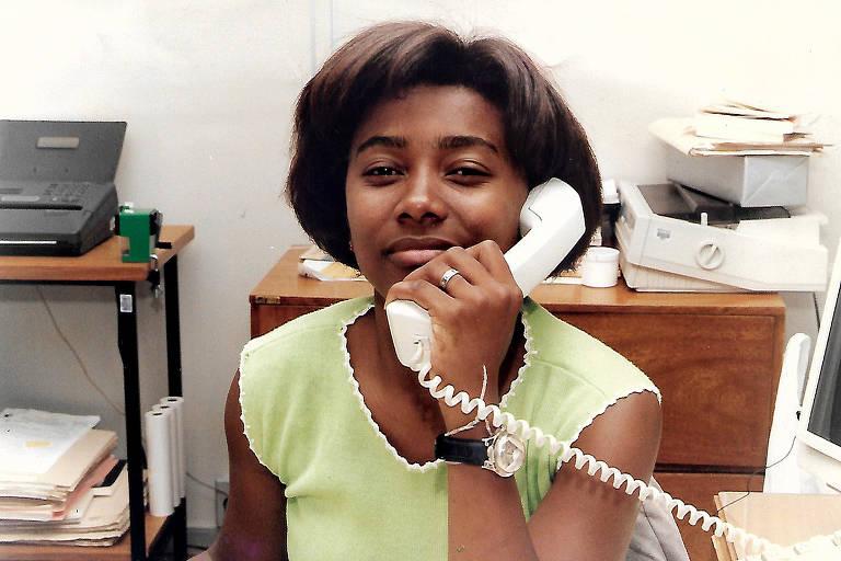 mulher negra jovem fala ao telefone sorrindo para foto