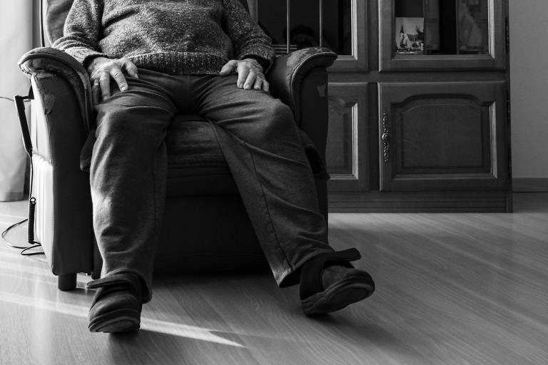 Homem velho sentado em poltrona, foto em preto e branco