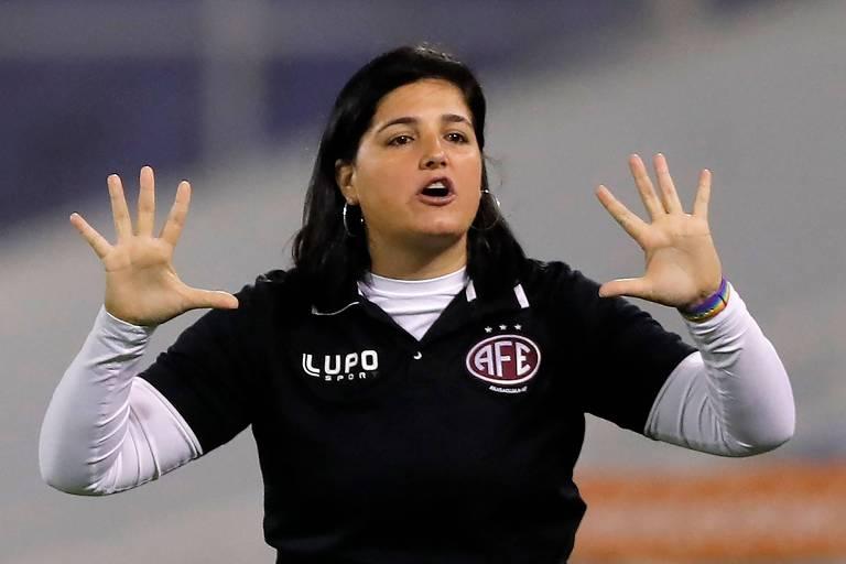 Mulher de blusa preta sobre uma branca e mãos espalmadas dá orientações a jogadoras