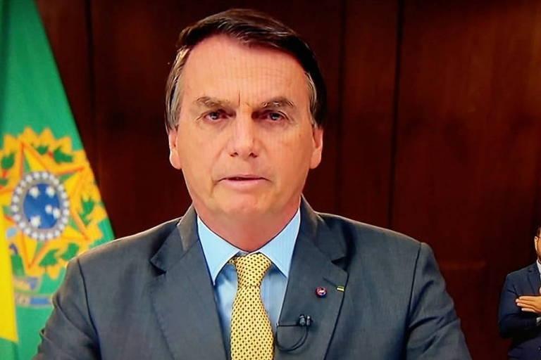 O presidente Jair Bolsonaro durante pronunciamento na TV. No canto inferior direito há um homem em tamanho pequeno fazendo a tradução em libras