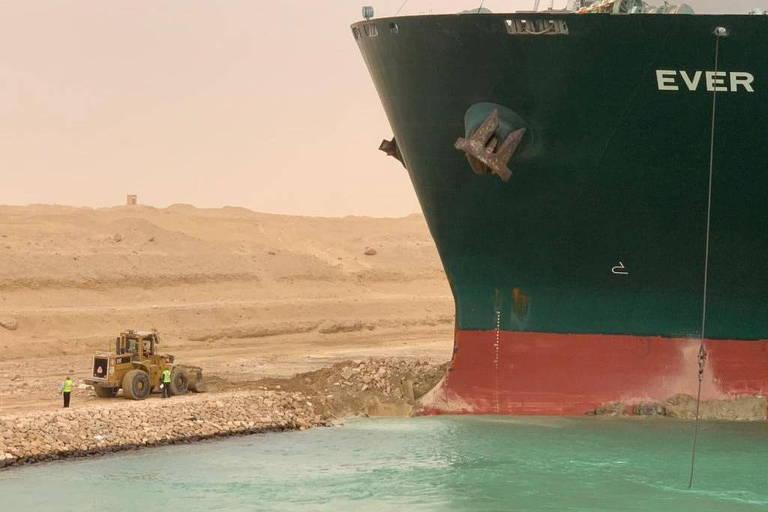 Trator escava região onde navio aterrou