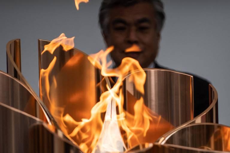 Homem observa fogo saindo de tocha