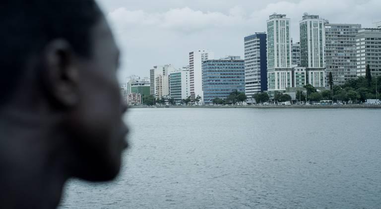 homem encara metrópole ao longe