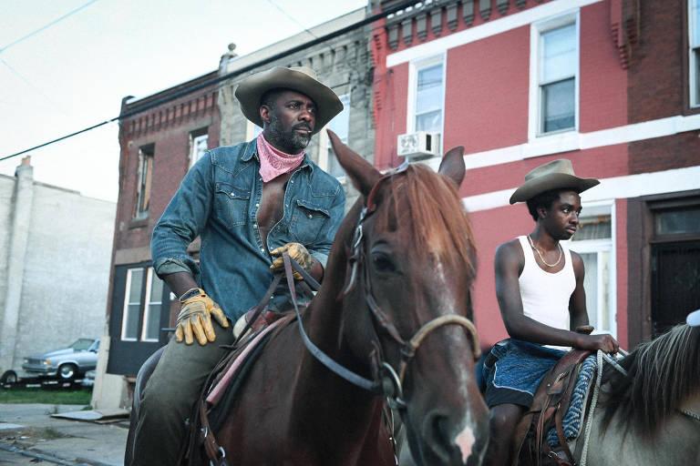 Atores Idris Elba e Caleb McLaughlin sobre cavalos em rua urbana